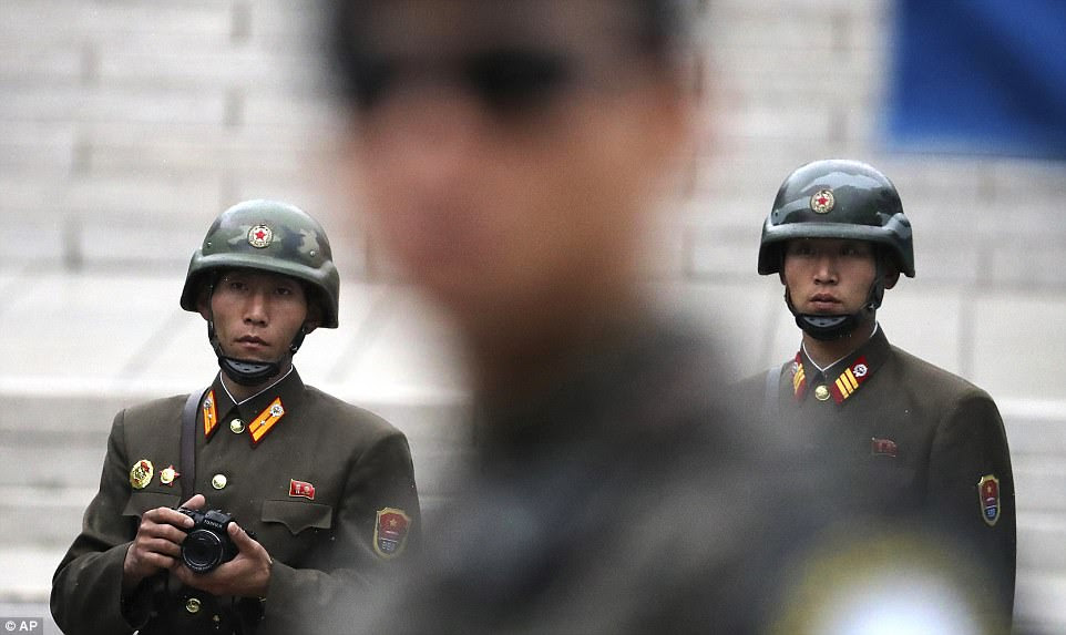 Two North Korean soldiers look at the south side as a South Korean soldier, center, stands guard while Pence visited the border village of Panmunjom