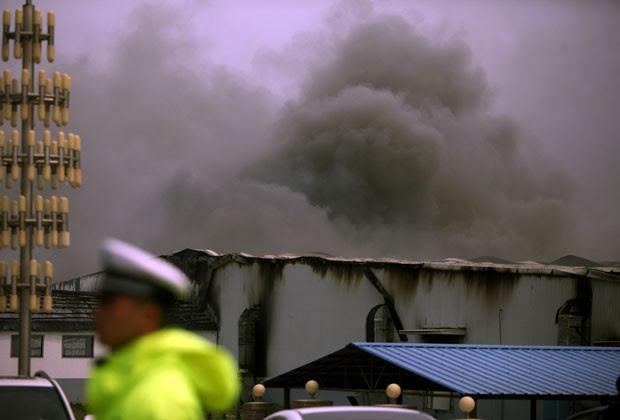 Fumaça sai de abatedouro de aves que pegou fogo na China; mais de 100 pessoas morreram (Foto: AFP)