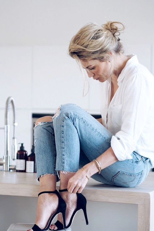 Le Fashion Blog Effortless Look Camilla Pihl Low Messy Bun White Button Down Top Stack Of Gold Bracelets Distressed Raw Hem Skinny Denim Black Ankle Strap High Heeled Sandals Via Camille Pihl