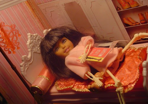 "The Doll Project: Ana reading in bed, a skeletal figure clinging to life and her ""How To Lose Weight"" book"