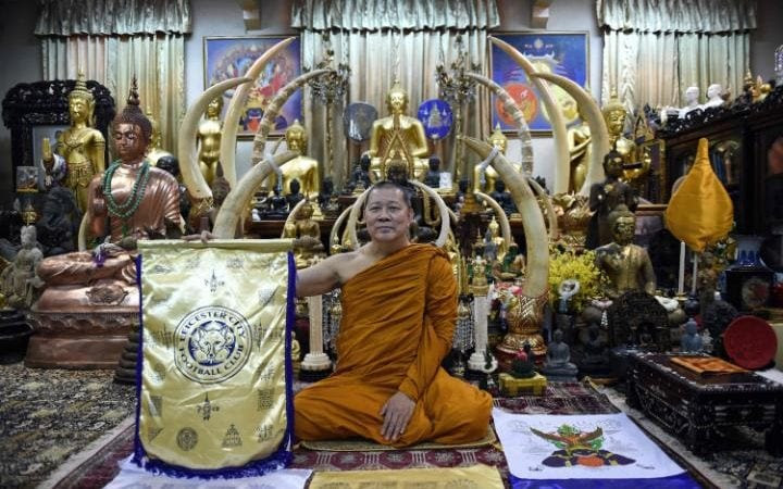 Thai Buddhist monk Phra Prommangkalachan holding a banner emblazoned with sacred patterns surrounding Leicester City Football Club's cres