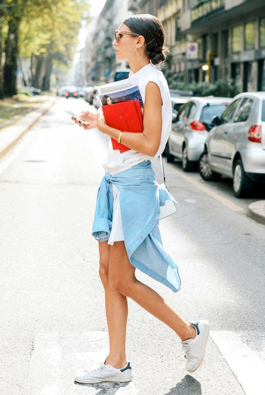 Le Fashion Blog Laid Back Street Style Low Bun Hoop Earrings White Sleeveless Shirtdress Denim Shirt Tied Around The Waist Adidas Stan Smith Sneakers Via Vogue