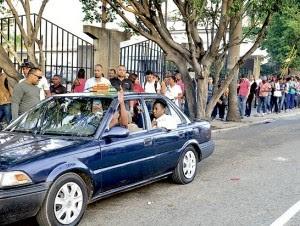 En horas pico, pasajeros forman largas filas para abordar un vehículo público.
