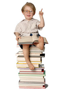 Photo: A boy sitting on a stack of books