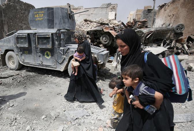 Des femmes en abaya noire fuient au milieu des ruines de la vieille ville de Mossoul avec leurs enfants dans les bras.