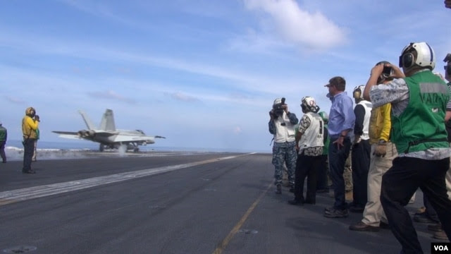 Bộ trưởng Quốc phòng Mỹ Ash Carter (mặc áo sơ-mi xanh, ở giữa) xem phi cơ cất cánh từ hàng không mẫu hạm USS John C. Stennis ở Biển Đông ngày 15/4/2016.