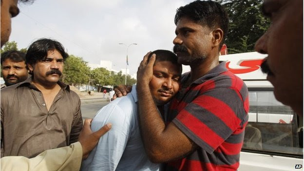 People comfort a relative of a killed airport worker, Karachi (9 June 2014)