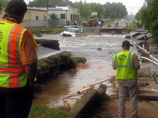 Officials look over the damage caused by the washout of Old Corry Field Road Wednesday in Pensacola, Fla.
