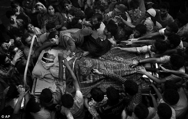 A sister of Feroz Ahmad, alias Showkat, who was killed by forces, wails as she clings to the bed carrying the body of her brother