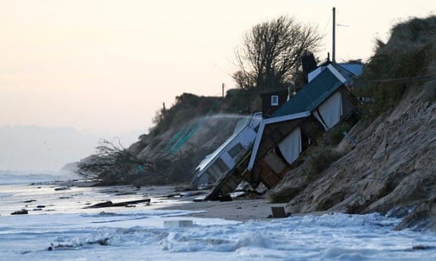 Collapsed houses lie on the beach after a storm surge in Hemsby, eastern England December 6, 2013