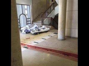 Marcas de sangue de corpos arrastados são vistas no chão da sinagoga palco do ataque a machados e facas em um bairro ultra-ortodoxo de Jerusalém. Ao fundo, corpos cobertos (Foto: Reuters/Zaka)