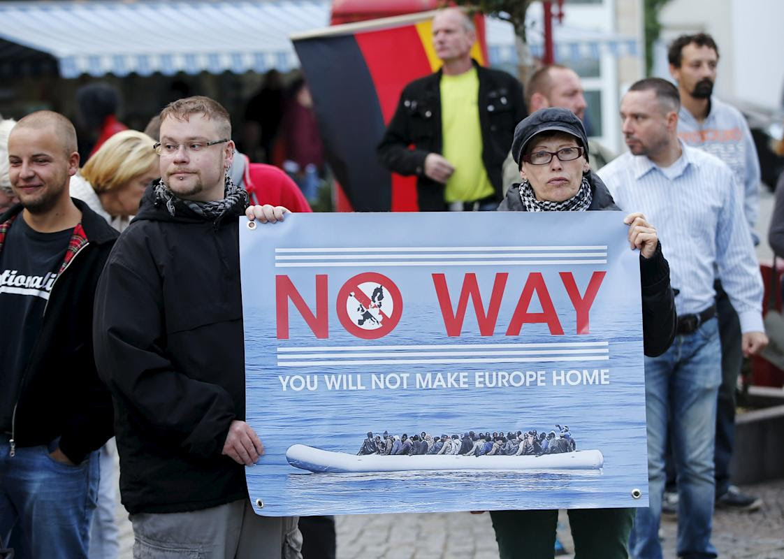 Supporters of the far-right National Democratic Party hold a placard and a German flag during a march in Riesa, Germany