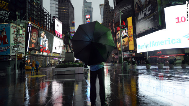 A lone tourist stands in Times Square early Monday as New Yorkers brace against Hurricane Sandy.