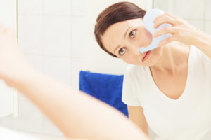 picture of a woman standing in front of the mirror using a neti pot.