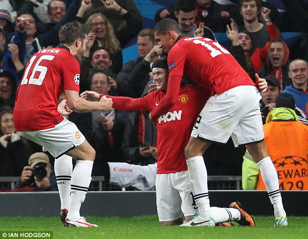 Mobbed: Rooney celebrates with Chris Smalling and Michael Carrick after his opening goal
