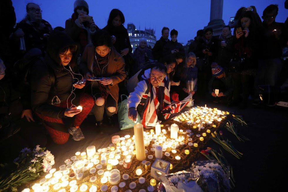 Un grupo de gente coloca velas en Trafalgar Square de Londres.