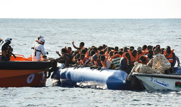 A migrant boat is greeted by coastguard rescuers