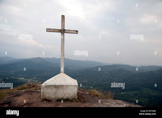Stock Photo - Cross on a mountain. A cross located on top of a hill near the tourist spot of Thekkady in Kerala, India with background view