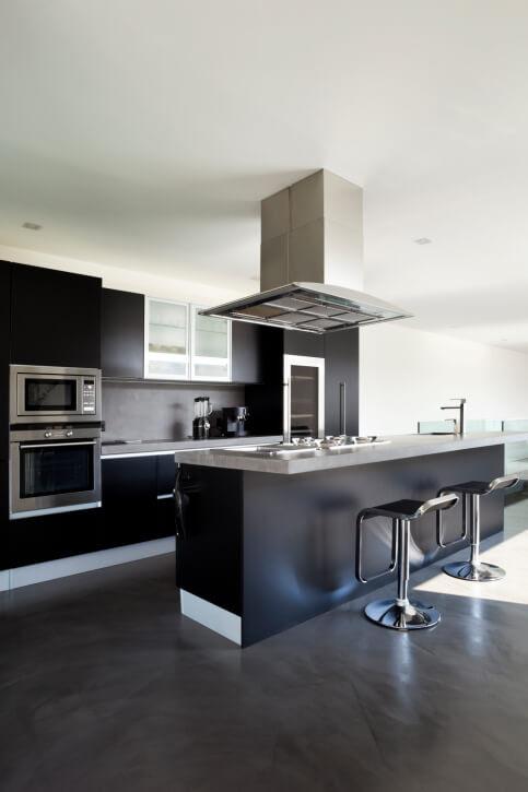Conception de cuisine moderne avec armoires noires sur sol brun foncé.