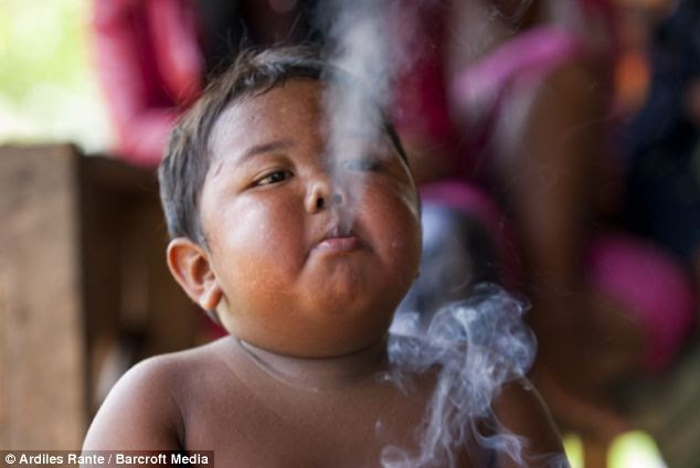 Destructive: The youngster was discovered in a poor village in Sumatra, Indonesia, puffing on a cigarette while riding his tricycle