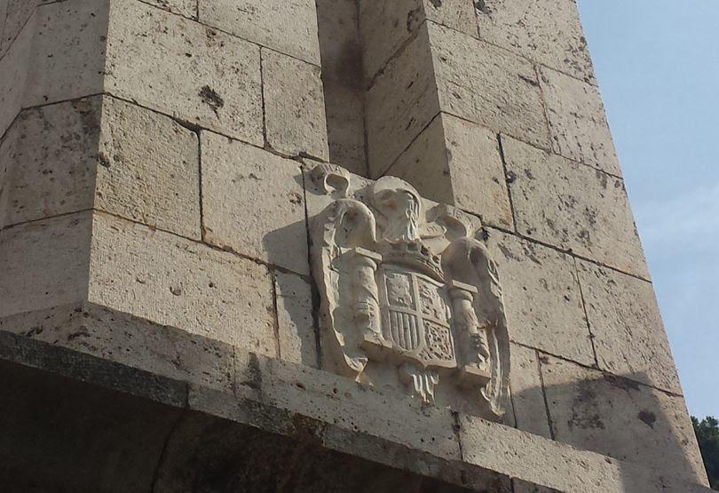 Detalle del escudo franquista a los pies de la cruz