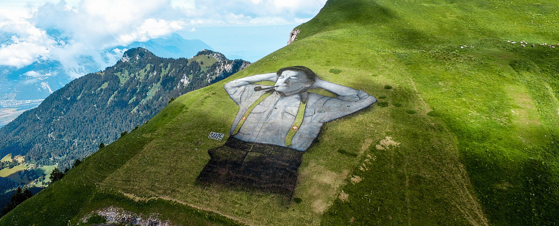 saype draws 10,000 square meter man in the mountains of leysin, switzerland