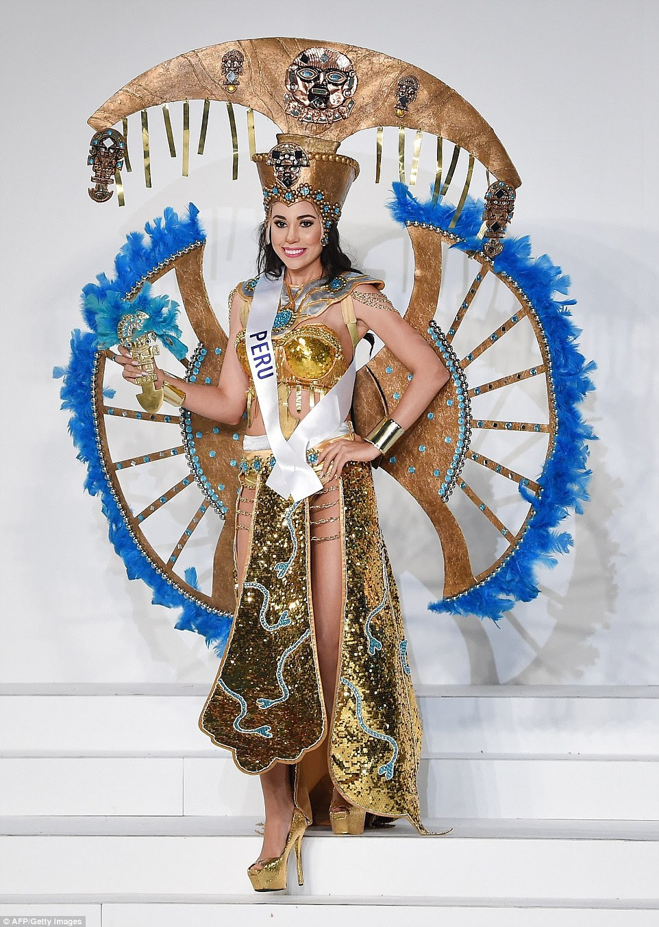 Miss Peru also impressed on the headwear stakes with what looks like an upside down herb chopper on her crown. Cynthia Lucia Toth Montoro's balance is perhaps helped by her fan-like golden wings, dotted with blue gems and fringed with blue feathers. Her look is completed with a golden sparkly skirt, shoes and cropped Madonna-esque bodice