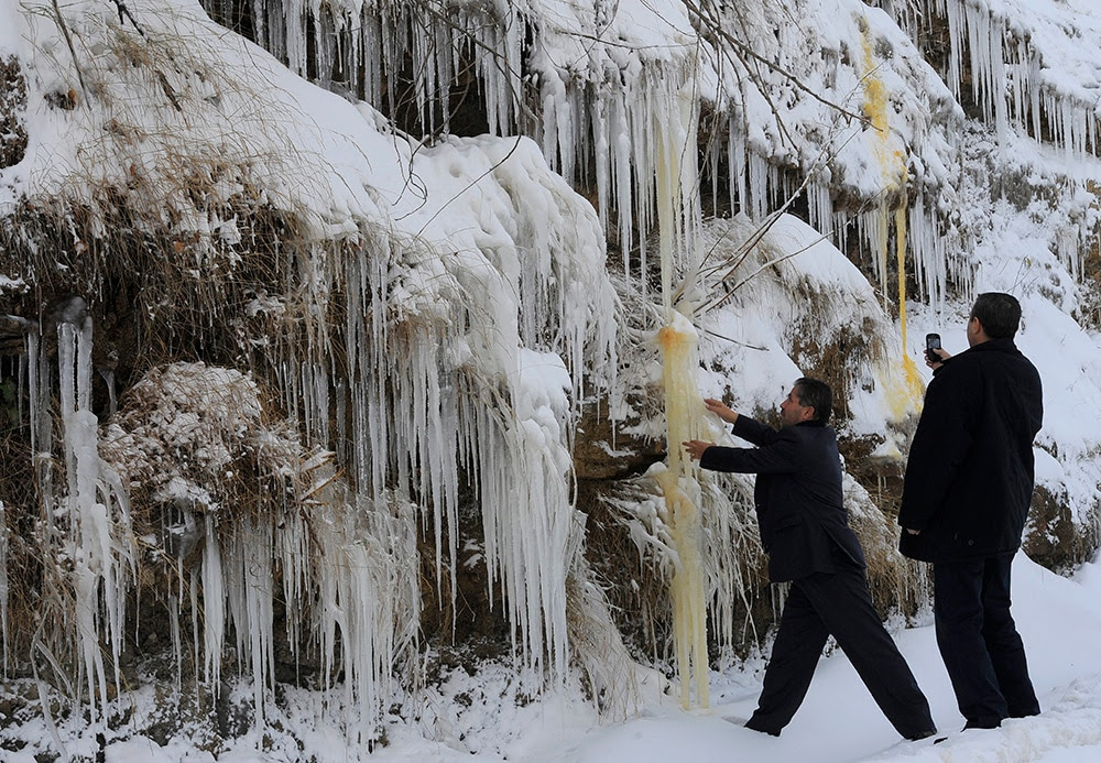 Lebanese men take pictures in front of the icicles in the village of Hammana southeast of Beirut. (EPA/WAEL HAMZEH)