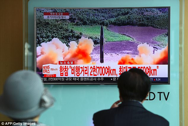 Living in fear: South Koreans watch  file footage of a North Korean missile launch, at a railway station in Seoul after the North fired a ballistic missile over Japan and into the Pacific Ocean