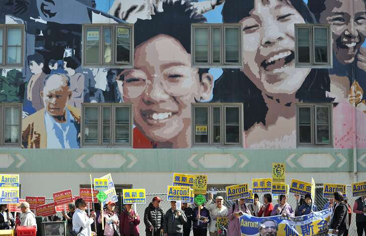 Political activists hold opposing signs in the Chinatown District of San Francisco on November 02, 2015.
