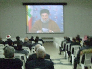 The leader of Hezbollah, Hassan Nasralla, for security reasons talking on video, here in a room adjacent to the packed lecture hall.