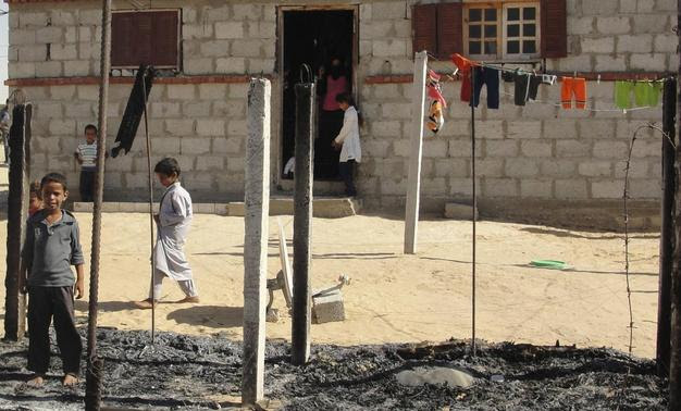 Boys look at a burnt area around a house after assaults on militant targets by the Egyptian Army, in a village on the outskirts of Sheikh Zuweid, near the city of El-Arish in Egypt's Sinai peninsula in this September 10, 2013 file photo. REUTERS-Stringer -Files