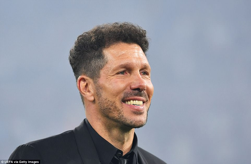 Atletico manager Diego Simeone smiles as he joins his players on the pitch following the conclusion of the match