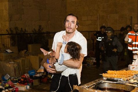 Volunteer carries wounded toddler to ambulance after Arab terror attack near Lion's Gate in Old City of Jerusalem.
