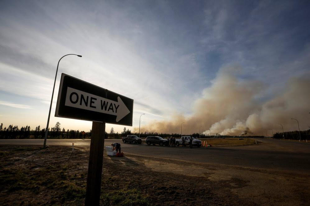 Una señal apunta hacia la inmensa humareda que ha generado el incendio.