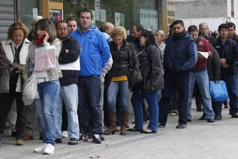 Decenas de personas hacen cola para entrar en una Oficina de Empleo de Madrid. | Reuters