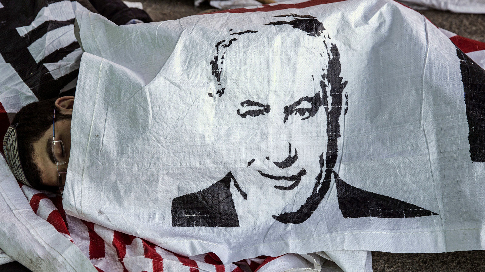 """An Israeli settler sleeps under a banner of Israeli Prime Minister Benjamin Netanyahu, in the Jewish settlement of Beit El after a night stand off with police, near the West Bank town of Ramallah, Wednesday, July 29, 2015. The Israeli Prime Minister's office said Wednesday it has approved the """"immediate construction"""" of 300 housing units in the West Bank settlement of Beit El. The announcement came amid a standoff, where Israeli settlers clashed with Israeli forces as authorities began to dismantle the contested West Bank settlement housing complex after Israel's Supreme Court ruled Wednesday that it must be demolished. (AP Photo/Tsafrir Abayov)"""