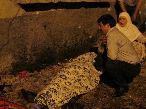 Homem chora ao lado de vítima de explosão em casamento em Gaziantep, na Turquia (Foto: Ihlas News/Reuters)