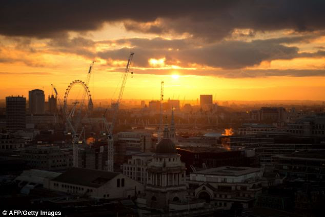 Misty dusk: As the sun sets over London this afternoon, the mist casts an orange glow through the capital