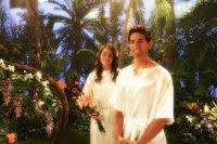 Adam and Eve stand in garden set.