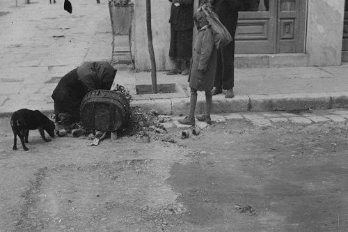 Woman searching for food in the garbage. Piraeus, crossroad of George the first and Praxitelous, winter 1941-1942.