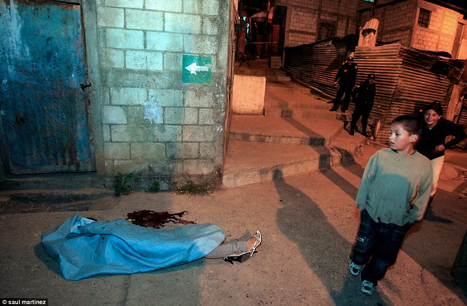 Shocking: A young boy walking through the streets of Guatemala City with his hands in his pockets glances at the body of a woman. Her high-heeled sandals poke out from beneath a blue sheet on the pavement of one of the most dangerous cities in the world