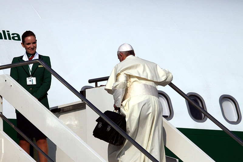 Pope Francis carries his bag up the stairs of the plane at Fiumicino airport, Rome. (EPA/TELENEWS)