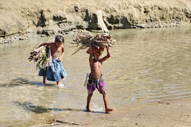 Two Rohingya children carries firewood crossing Tamru canal that has divided Bangladesh and Myanmar along Bangladesh's Naikhong chhari border in Bandarban district. Several thousand Rohingya people are still staying i no man's land along Naikhongchhari border. Credit: Farid Ahmed/IPS