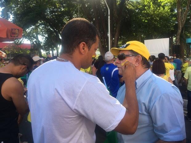 Manifestantes pintam os rostos com as cores da bandeira do Brasil (Foto: Camilla Motta/G1)
