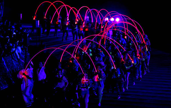 Performers hold illuminated rods during the opening ceremony of the 2012 Summer Olympics on Friday.