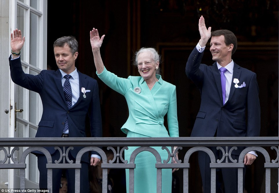 On the balcony: Queen Margrethe, her heir Frederik (left) and her younger son Joachim wave to the crowds