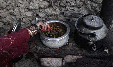 Seorang wanita pengungsi Afghanistan memasak makanan untuk berbuka puasa di Kabul, Afghanistan, Senin (22/7). (AP/Rahmat Gul)