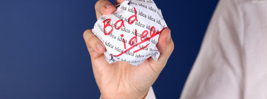 "Crumpled paper ball with red words ""Bad idea"" and background with words ""idea"" in woman hand."