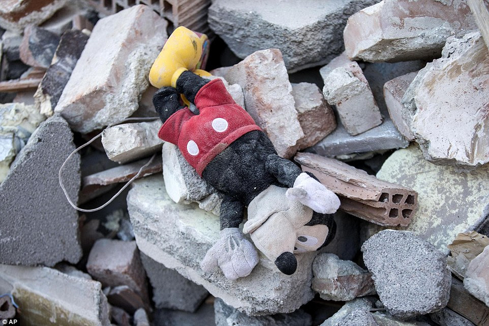A Mickey Mouse doll lies amidst the debris of a collapsed house following the earthquake in Amatrice